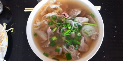 Beef pho in a white bowl.