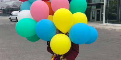 A girl holds balloons outside of E5.